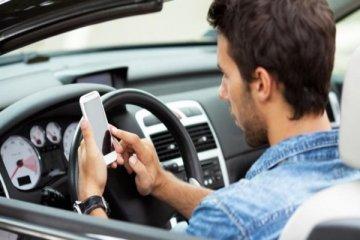 ragazzo di profilo che guida un'auto e contemporaneamente usa il cellulare