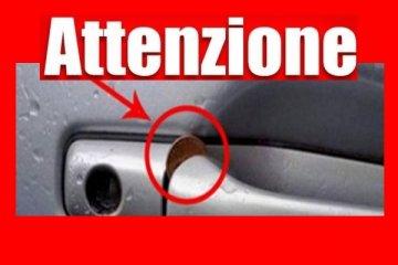 """monetina incastrata nella maniglia di auto auto per una truffa, freccia che evidenzia la moneta e scritta bianca """"Attenzione"""" su sfondo rosso"""